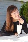 Muchacha hermosa que bebe un milkshake con una paja Fotografía de archivo
