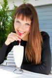 Muchacha hermosa que bebe un milkshake con una paja Foto de archivo libre de regalías