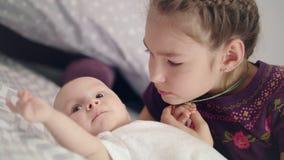 Muchacha hermosa que besa al bebé que miente en el sofá Hermano recién nacido del beso de la hermana almacen de metraje de vídeo