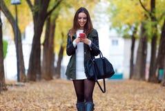 Muchacha hermosa que camina con el teléfono móvil en otoño Imagen de archivo