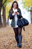 Muchacha hermosa que camina con el teléfono móvil en otoño Imagenes de archivo