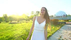 Muchacha hermosa que camina divirtiéndose en hierba verde en día de verano del parque en puesta del sol del sol Felicidad de la s almacen de video