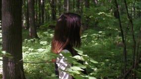 Muchacha hermosa que camina en el bosque verde frondoso almacen de metraje de vídeo