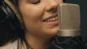 Muchacha hermosa que canta en estudio de los sonidos Cantante joven que registra emocionalmente la nueva canción La señora canta  metrajes