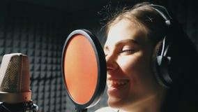 Muchacha hermosa que canta en estudio de los sonidos Cantante joven que registra emocionalmente la nueva canción La señora canta  almacen de metraje de vídeo