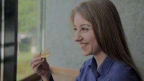 Muchacha hermosa que celebra las patatas fritas en un restaurante de comida r?pida almacen de video