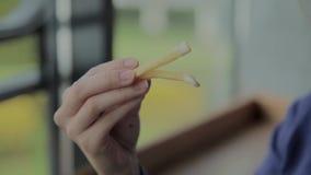Muchacha hermosa que celebra las patatas fritas en un restaurante de comida r?pida almacen de metraje de vídeo