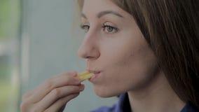 Muchacha hermosa que celebra las patatas fritas en un restaurante de comida r?pida metrajes