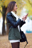 Muchacha hermosa que charla con el teléfono móvil en otoño Imagen de archivo