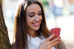 Muchacha hermosa que charla con el teléfono móvil en otoño Fotos de archivo libres de regalías