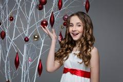Muchacha hermosa que coloca el árbol cercano con las decoraciones de la Navidad Imagenes de archivo