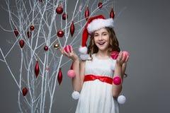 Muchacha hermosa que coloca el árbol cercano con las decoraciones de la Navidad Fotografía de archivo