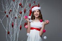 Muchacha hermosa que coloca el árbol cercano con las decoraciones de la Navidad Imágenes de archivo libres de regalías