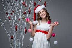 Muchacha hermosa que coloca el árbol cercano con las decoraciones de la Navidad Fotos de archivo