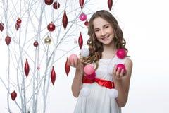Muchacha hermosa que coloca el árbol cercano con las decoraciones de la Navidad Imagen de archivo