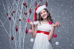 Muchacha hermosa que coloca el árbol cercano con las decoraciones de la Navidad Foto de archivo libre de regalías