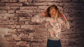 Muchacha hermosa que coloca la pared cercana, el salto, el baile y jugando con el pelo, sacudiendo su cabeza metrajes