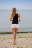 Muchacha hermosa que coloca y que mira el mar, haciendo frente al amanecer Fotografía de archivo