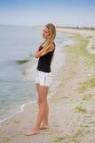 Muchacha hermosa que coloca y que mira el mar, haciendo frente al amanecer Fotos de archivo