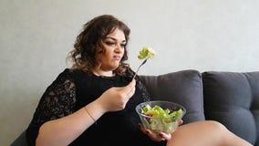 Muchacha hermosa que come el almuerzo de la ensalada el aperitivo hambriento de la emoción del repugnancia del asombro del sofá d metrajes