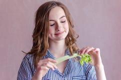 Muchacha hermosa que come el apio Fotografía de archivo libre de regalías