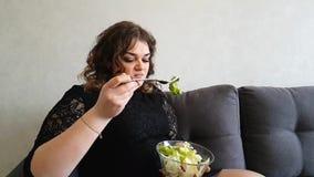 Muchacha hermosa que come la ensalada el aperitivo hambriento de la emoción del repugnancia del sofá almacen de metraje de vídeo