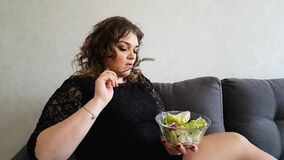 Muchacha hermosa que come la ensalada el aperitivo hambriento de la emoción del sofá almacen de video