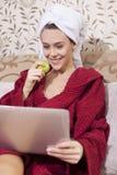 Muchacha hermosa que come la manzana y que mira noticias Imágenes de archivo libres de regalías
