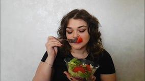 Muchacha hermosa que come la placa de la emoción de la balanza de la ensalada almacen de video