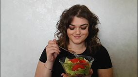 Muchacha hermosa que come la placa vegetal de la emoción de la balanza de la ensalada metrajes