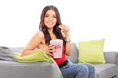 Muchacha hermosa que come las palomitas asentadas en un sofá Foto de archivo