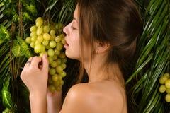 Muchacha hermosa que come las uvas Foto de archivo