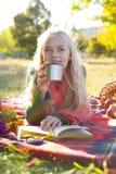 Muchacha hermosa que come té al aire libre Foto de archivo