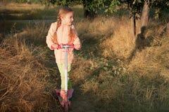 Muchacha hermosa que conduce la vespa en el camino rural Imágenes de archivo libres de regalías
