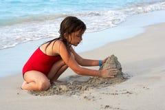 Muchacha hermosa que construye un castillo de la arena en la playa Imagenes de archivo