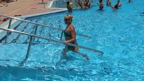 Muchacha hermosa que deja la piscina después de bañar Mujer joven que disfruta de días de fiesta tropicales almacen de video