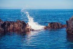 Muchacha hermosa que descansa en piscina natural del océano Foto de archivo