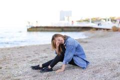 Muchacha hermosa que descansa, sentándose por el mar y presentando en cámara en b fotografía de archivo libre de regalías