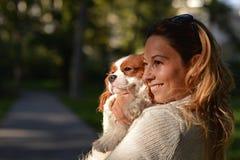 Muchacha hermosa que detiene a su rey arrogante Charles Spaniel del perro fotografía de archivo