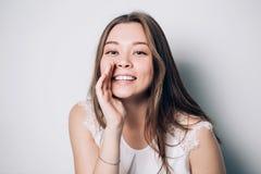 Muchacha hermosa que dice un secreto Mujer feliz joven del retrato Susurro modelo de la muchacha divertida sobre algo imagenes de archivo
