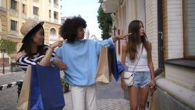 Muchacha hermosa que elige la ropa durante compras metrajes