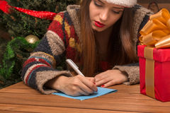 Muchacha hermosa que escribe la enhorabuena del Año Nuevo y de la Navidad Imagen de archivo