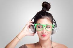 Muchacha hermosa que escucha la música con los auriculares Foto de archivo