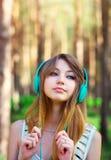 Muchacha hermosa que escucha la música con los auriculares Foto de archivo libre de regalías