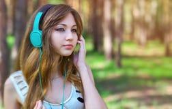 Muchacha hermosa que escucha la música con los auriculares Imágenes de archivo libres de regalías