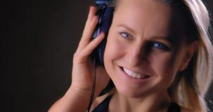 Muchacha hermosa que escucha la música con los auriculares almacen de metraje de vídeo