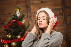 Muchacha hermosa que escucha la música delante del árbol del Año Nuevo Foto de archivo libre de regalías