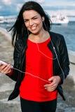 Muchacha hermosa que escucha la música en la costa Imagen de archivo