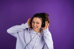 Muchacha hermosa que escucha los auriculares que llevan de la música en una camiseta en un fondo púrpura Foto de archivo libre de regalías