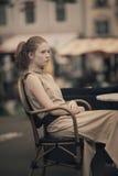 Muchacha hermosa que espera en la tabla en café Fotos de archivo